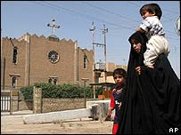 An Iraqi woman with her children walks past a Chaldean Christian church in eastern Baghdad