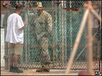 A detainee, left, talks with a guard through a fence at Guantanamo Bay (file photo)