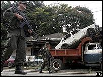 Policías caminan por las calles de Corinto, Colombia, cerca de donde se lleva a cabo la búsqueda de los restos humanos