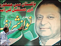 A man cleans a poster of Nawaz Sharif in Islamabad, Pakistan