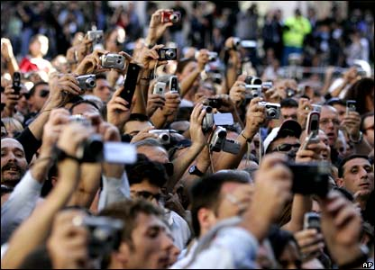 People uses their cameras as the coffin of late Italian tenor Luciano Pavarotti leaves the cathedral
