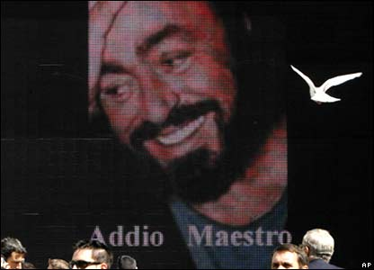 "People wait, in front of a screen displaying a picture of Luciano Pavarotti that reads in Italian ""Farwell Maestro""."