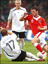 Wales' Jason Koumas is tackled by Germany's Per Mertesacker