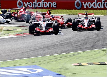 Fernando Alonso leads round the first corner from Lewis Hamilton (right) and Felipe Massa