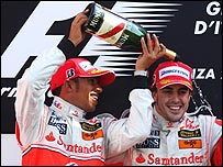 Lewis Hamilton pours champagne over winner Fernando Alonso on the Italian Grand Prix podium