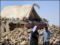 Two Iraqis survey the rubble from a suicide lorry bombing in the village of Qataniya on 19 August.