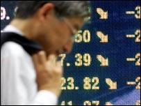 رجل أعمال ياباني أمام لوحة لأسعار الأسهم