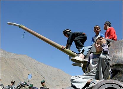 Afghan boys rest on a destroyed tank in Panjshir, Afghanistan