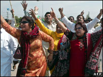 PML-N activists celebrate Nawaz Sharif's arrival during a demonstration near the Islamabad airport