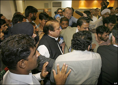 Nawaz Sharif, centre, is escorted by Pakistani police as he is apprehended shortly after his arrival in Islamabad from London.