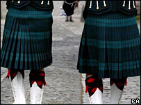 Two people wearing kilts