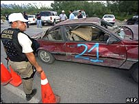 Cars damaged in the blast are towed away