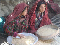 Two Afghan women sifting wheat