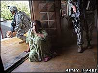 An Iraqi woman waits as US soldiers search her home in Baghdad