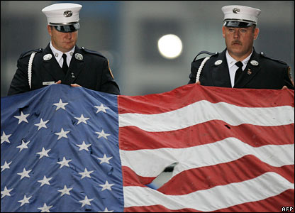 Firefighters hold a US flag damaged in the 9/11 attacks at a sixth anniversary ceremony