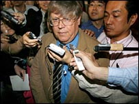 Man being besieged by reporters