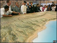 Dignitaries and reporters stand next to a model of Libya's coast