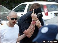 Un policía israelí traslada a un miembro de la banda al tribunal en Tel Aviv