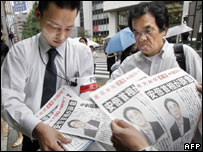 People  buy extra edition newspapers reporting Prime Minister Shinzo Abe's resignation in Tokyo - 12 September 2007