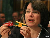Senator Amy Klobuchar holds a toy train containing lead paint