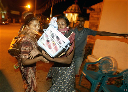 Sri Lankan women rush with their belongings to safer area, after a tsunami warning in Colombo