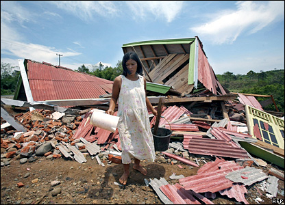 A resident salvages items from her home in Air Besi in North Bengkulu, Indonesia