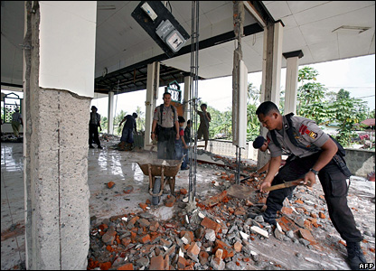 Indonesian policemen clean debris from a damaged mosque in Bengkulu, Indonesia