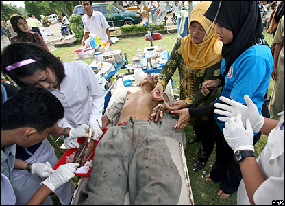 A man injured in the earthquake is treated in the open air at a hospital in Bengkulu, Indonesia