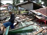 Un hombre camina sobre los restos de su casa en Bengkulu.