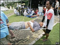 Rescuers carry an injured man on a stretcher at a makeshift hospital in Bengkulu, Sumatra