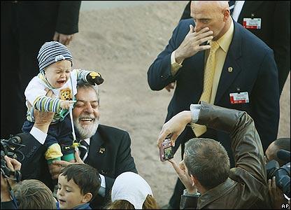 Brazilian President Luiz Inacio Lula da Silva, holds a baby in Norway