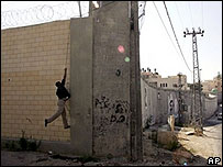 Palestinian man scales Israeli barrier in Abu Dis