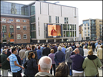 A crowd watches the funeral on a big screen in Millennium Square