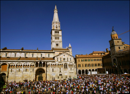 People are gathered in front of Modena's Romanesque cathedral