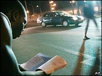 Guinean student reviews his school notes using the car park lights