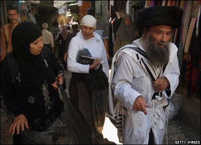 An ultra-Orthodox Jewish man and his wife pass Palestinians in the Muslim Quarter of the Old City of Jerusalem.