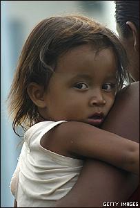 Una niña nicaragüense aguarda en brazos de su madre la asistencia humanitaria de la Marina estadounidense en Puerto Cabezas, al norte del país