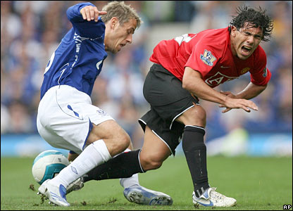 Phil Neville tackles Carlos Tevez