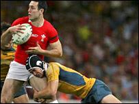 Wales fly-half Stephen Jones is tackled by opposite number Berrick Barnes