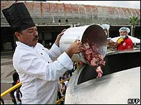 A cook throws meat inside a huge pot to make the sancocho
