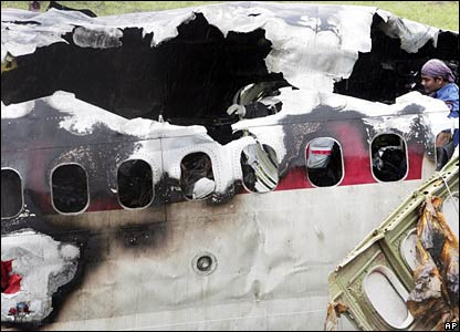 Rescuers examine a large hole in the fuselage of the charred plane