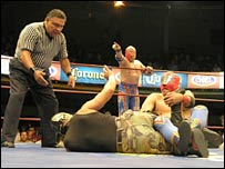 Referee stands over two luchadores in the ring