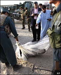 Afghan officials carry the body of an alleged suicide bomber, Kabul, 2 September 2007