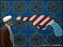 An Iranian cleric walks past a mural on the wall of the former US embassy in Tehran (February 2007)