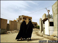 Iraqi women walk past security walls in the Karrada district of Baghdad