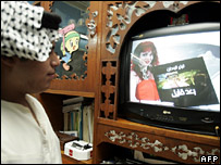 A Baghdad resident watches television