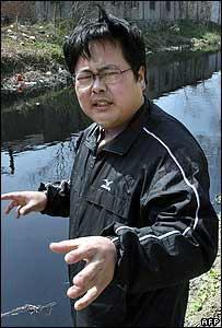 Wu Lihong by a polluted and blackened canal outside a factory in Yixing, 16 March 2006