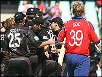 Stuart Broad (right) trudges off as New Zealand celebrate victory