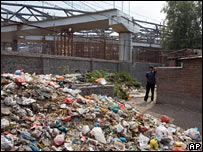 A man walks past a pile of rubbish near the petitioners' village on 6 September 2007