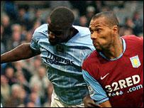 Micah Richards challenges Aston Villa striker John Carew